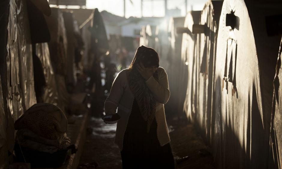 A Syrian refugee woman is seen between a line of tents in a refugee camp near Azaz, north of Aleppo province, Syria. Photo: Manu Brabo, AP