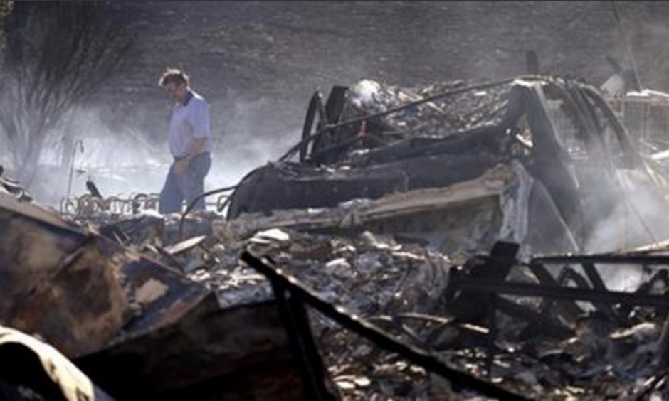Vern Smith walks through the rubble of his still smoldering home on June 29, 2015, one of some two dozen destroyed in a wildfire the night before, in Wenatchee, Wash. Photo: Elaine Thompson, AP