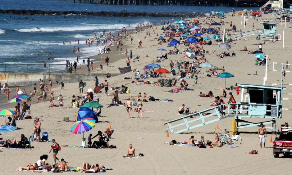 In this Feb. 15, 2016, file photo swimmers and sunbathers gather at Redondo Beach, Calif. El Nino has so far left much of drought-stricken California in the dust, delivering a few quick storms but not yet bringing the legendary rain previously linked to the periodic ocean-warming phenomenon. Image: John Antczak, AP Photo