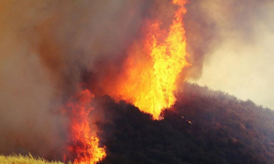 "A wildfire in northern Los Angeles County gains ferocious new power two days after it broke out in Placenta Caynon Road in Santa Clarita, Calif., Sunday, July 24, 2016. Flames raced down a steep hillside ""like a freight train,"" leaving smoldering remains of homes and forcing thousands to flee the wildfire churning through tinder-dry canyons in Southern California, authorities said Sunday. Photo: Matt Hartman / AP"