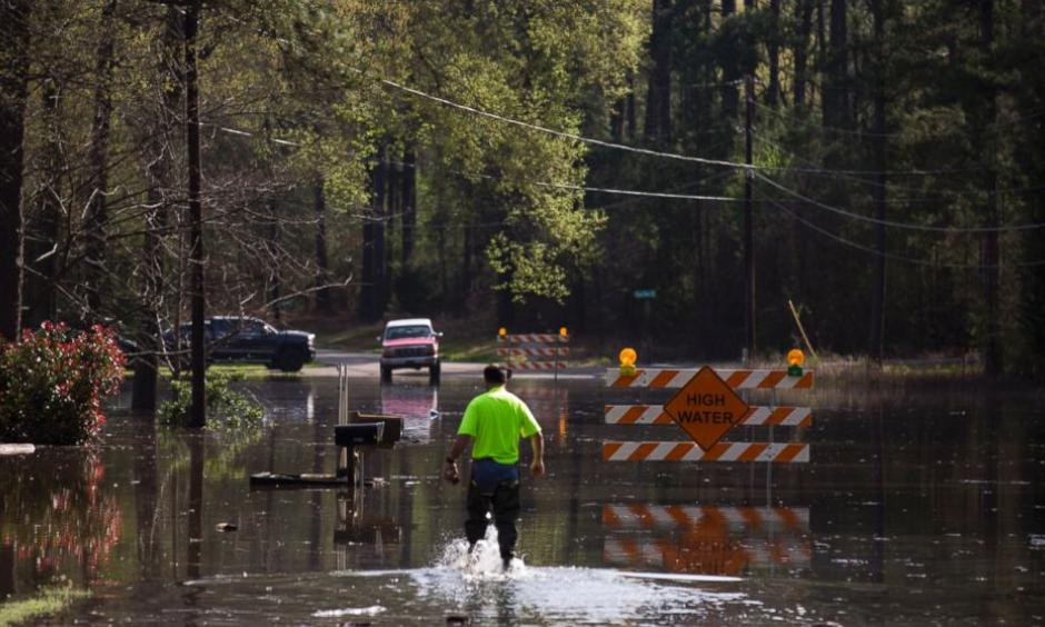 A man walks through floodwaters from Caddo Lake in Mooringsport, La., Sunday, March 13, 2016. President Barack Obama has signed an order declaring Louisiana's widespread flooding from heavy rains a major disaster. Photo: Lee Celano/The Shreveport Times via AP
