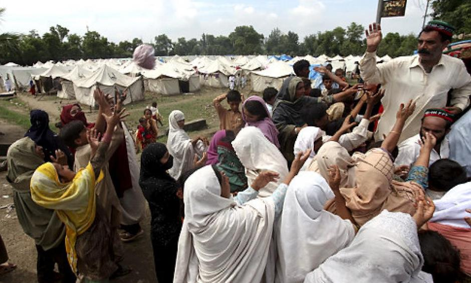 Flood-affected crowds get relief food at a camp in Nowshera, northwest Pakistan, on Monday. The number of people suffering from the disaster now exceeds 13 million. Photo: Sajjad, AP