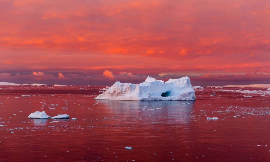 A startling sunset reddens the Lemaire Channel, off the west coast of the Antarctic Peninsula. The continent's coastal ice is crumbling as the sea and air around it warm. Photo: Camille Seaman