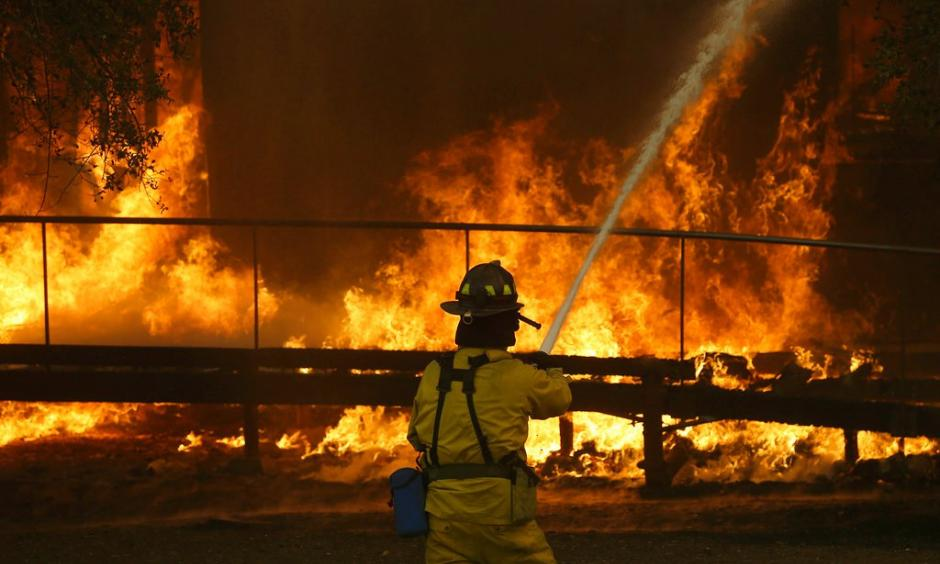 A firefighter sprays a hose into a Keysight Technologies building in Santa Rosa last month during the wildfires that killed 42 people and destroyed 8,700 homes and buildings. Photo: Jeff Chiu, Associated Press Photo