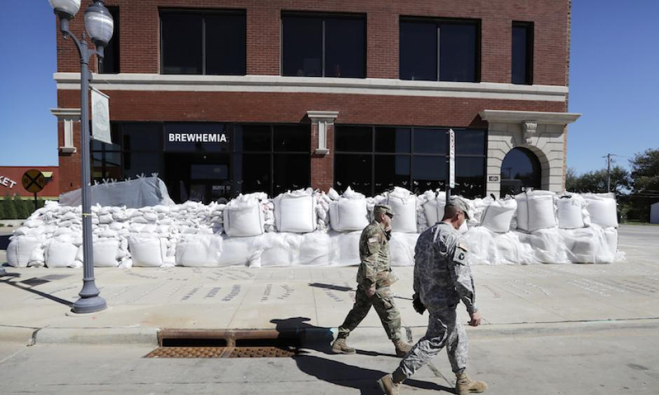 Iowa National Guard members walk past a local business covered in sandbags, Monday, Sept. 26, 2016, in Cedar Rapids, Iowa. Residents are waiting anxiously as a quickly rising Cedar River threatens to inundate their city with devastating floodwaters for the second time in eight years. Photo: Charlie Neibergall, AP