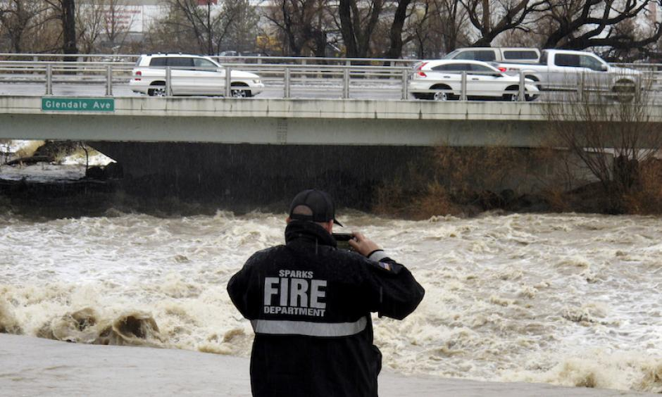 A firefighter from Sparks, NV, takes a picture of the rising Truckee River on Sunday, January 8, 2017, where it runs near the Grand Sierra hotel-casino along a line that divides the cities of Reno and Sparks. Photo: Scott Sonner, AP