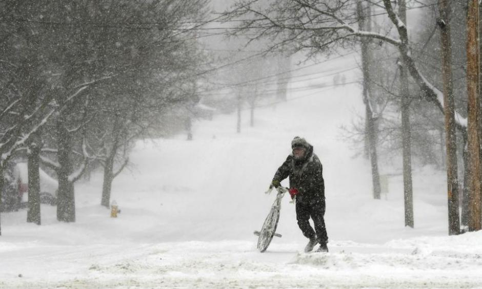 Jake Robinson walks his bike during a winter storm in Auburn, New York, Tuesday, March 14, 2017. A blustery, late-season storm clobbered the Northeast with sleet and heavy snow Tuesday, crippling much of the Washington-to-Boston corridor after a stretch of unusually mild winter weather that had people thinking spring was already here. Photo: Kevin Rivoli, The Citizen via AP