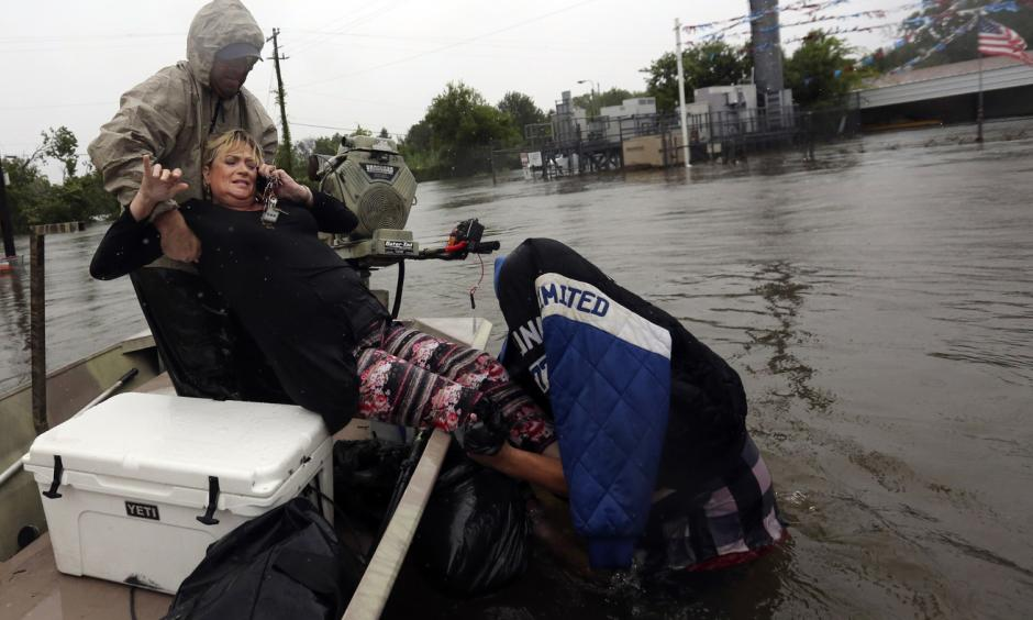 Rhonda Worthington is lifted into a boat while on her cellphone with a 911 dispatcher on Monday in Houston. Houston and other areas along the Gulf Coast are facing intense flooding from Tropical Storm Harvey. Photo: LM Otero, AP