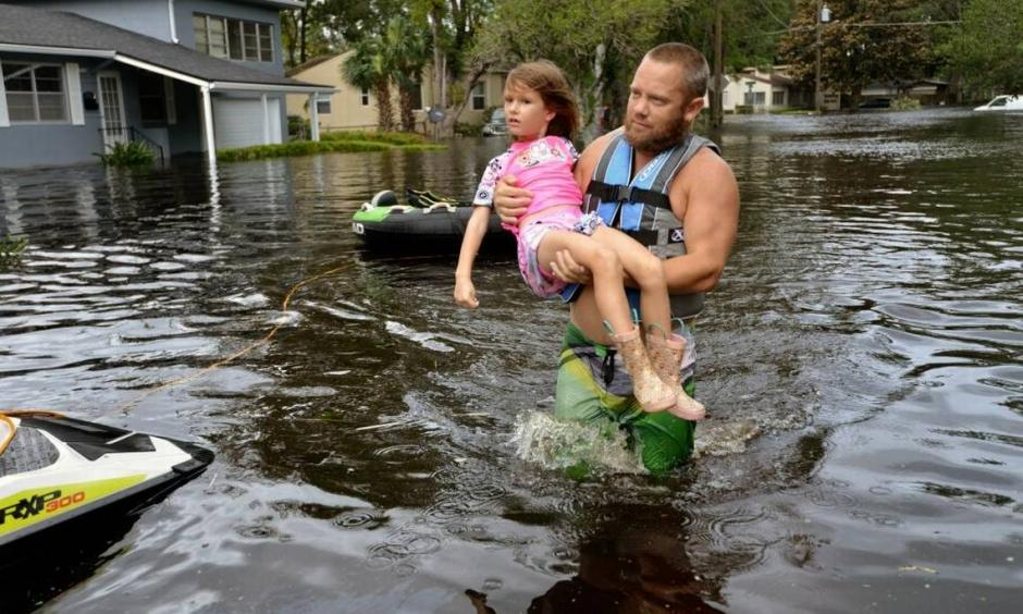 Tommy Nevitt carries Miranda Abbott, 6, through flooding caused by Hurricane Irma on the west side of Jacksonville, Monday, Sept. 11 2017. Photo: Dede Smith, The Florida Times-Union via AP