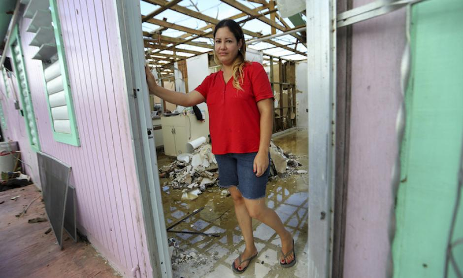 "In this photo from Thursday, September 28, 2017, Sandy Nieves stands in the doorway of her heavily damaged home in the aftermath of Hurricane Maria in Yabucoa, Puerto Rico. Nieves said her greatest need is her home and especially her baby's bed. ""We don't have anywhere to sleep, we don't have our stuff. We are all sleeping in one bed at my mom's house."" Photo: Gerald Herbert, AP"