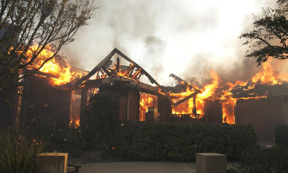 Flames from a wildfire consume a home Monday, east of Napa, Calif. Photo: Rich Pedroncelli, AP