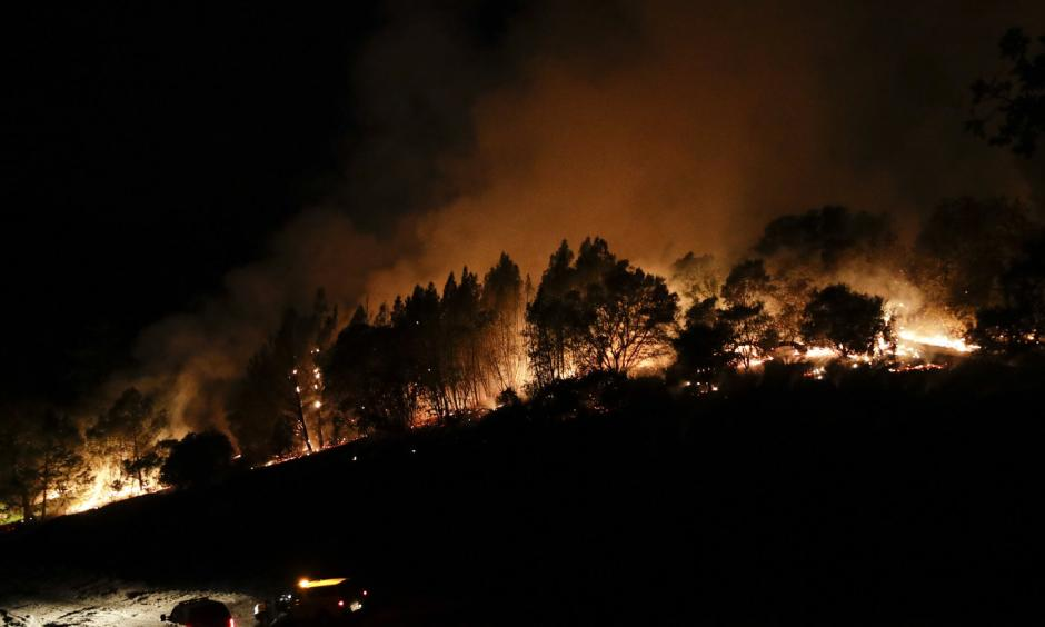 Firefighters watch from their fire trucks as wildfires continue to burn on Thursday, near Calistoga, Calif. Jae C. Hong/AP