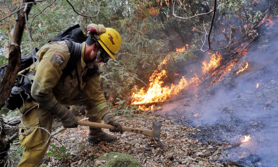 A firefighter builds a containment line as he battles a wildfire Tuesday, Oct. 17, 2017, near Boulder Creek, California. Photo: Marcio Jose Sanchez, AP