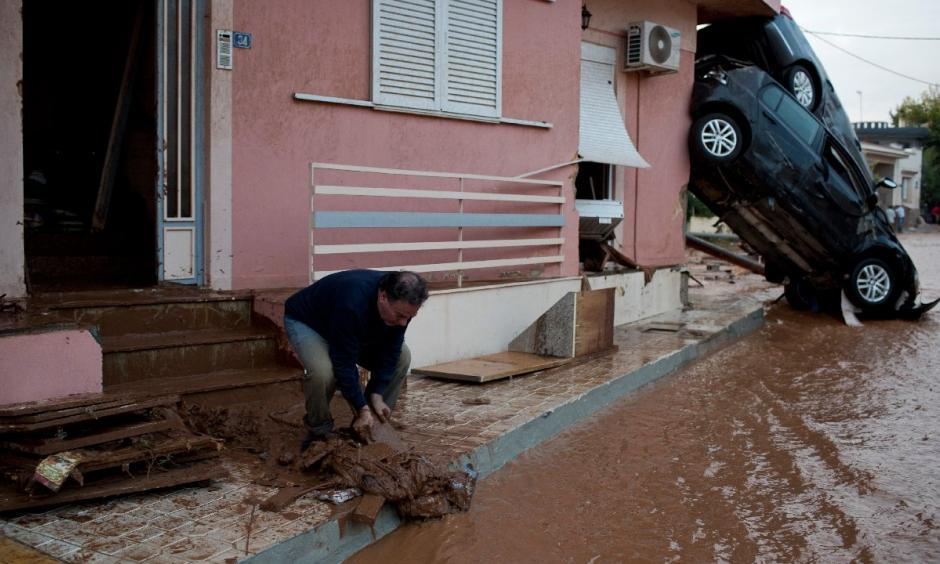 A man clears mud from his home in front of flipped over cars in the municipality of Mandra western Athens, on Wednesday, Nov. 15, 2017. Photo: Petros Giannakouris, AP