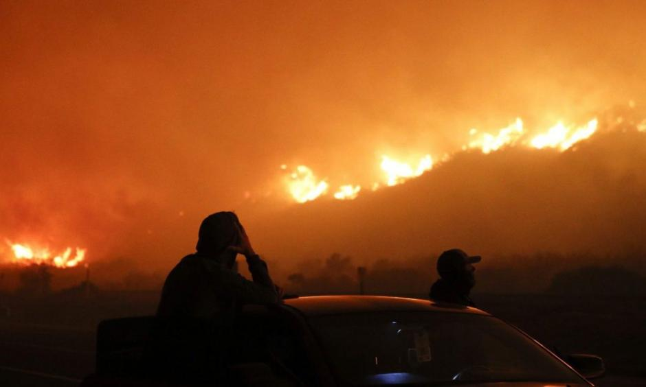 Two spectators watch as a wildfire burns along the 101 Freeway Tuesday, Dec. 5, 2017, in California. Photo: Jae C. Hong, AP