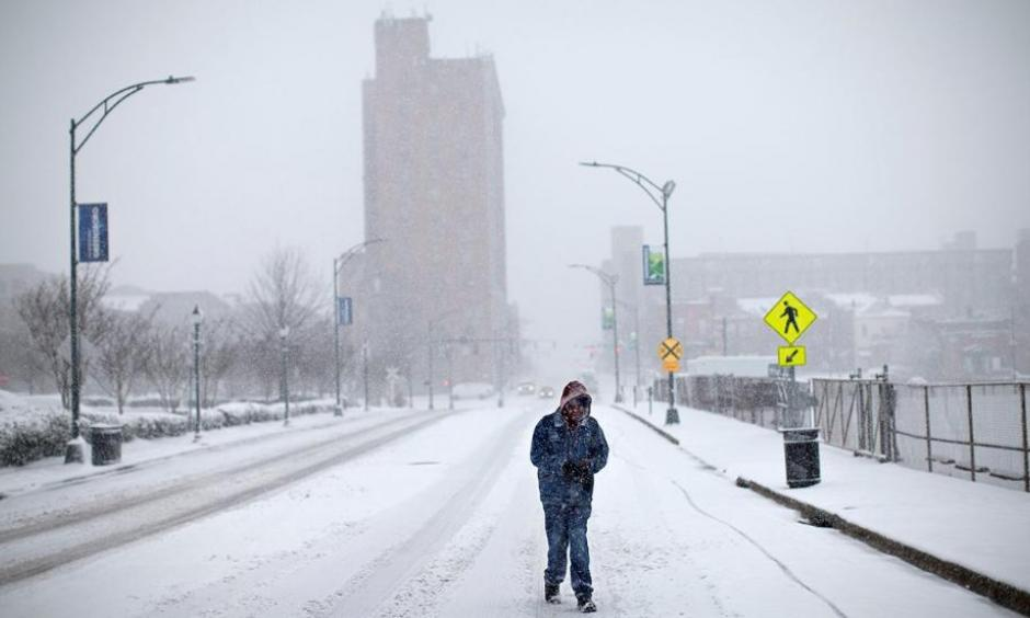 A pedestrian walks down the middle of Washington Street, Wednesday, Jan. 17, 2018, in Greensboro, N.C. The National Weather Service has issued a winter storm warning for Greensboro with a snow accumulation between 4-7 inches expected. Photo: Andrew Krech, News & Record via AP
