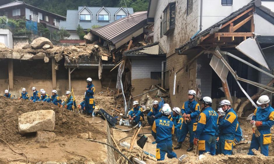 Emergency teams rest outside of structural damage caused by heavy rains, Monday, July 9, 2018, in Hiroshima, Japan. Credit: Haruka Nuga, AP