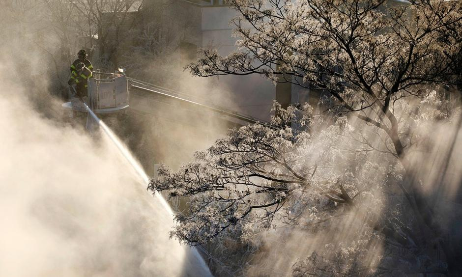 Ice forms on tree branches as New York firefighters battle a blaze in a commercial building in the Bedford Stuyvesant neighborhood of Brooklyn, Thursday, Jan. 31, 2019 in New York. Firefighters around New York state have been grappling with brutal cold during big blazes. Photo: Mark Lennihan, AP