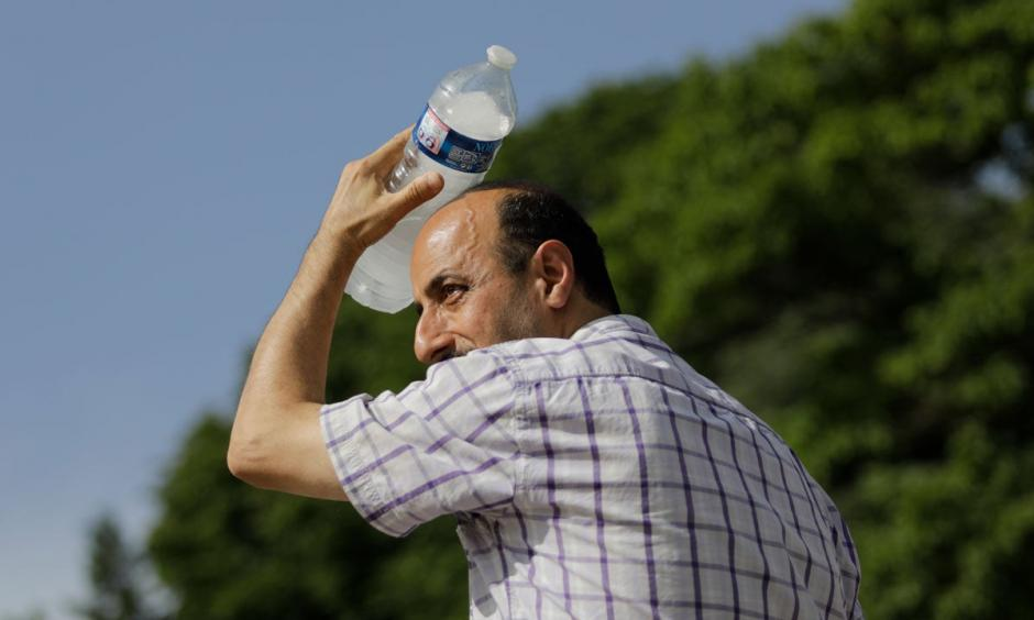 A man uses a cool bottle of water to cool off in the Trocadero gardens in Paris, Friday, June 28, 2019. Credit: Lewis Joly, AP