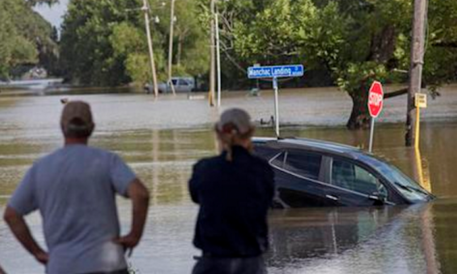 In this Aug. 16, 2016 file photo, residents survey the flood water on Old Jefferson Highway at Bayou Manchac in Prairieville, La. The flooding killed at least 13 people, damaged 150,000 homes and cost at least $8.7 billion. Photo: Max Becherer, AP