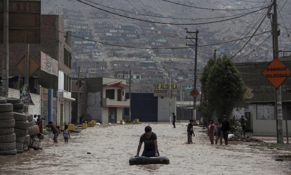 A man plays in a flooded street using an inner tube in Lima, Peru, Thursday, March 16, 2017. A new round of unusually heavy rains has killed at least a dozen people in Peru and now threatens flooding in the capital. Authorities said Thursday they expect the intense rains caused by the warming of surface waters in the eastern Pacific Ocean to continue another two weeks. Photo: Rodrigo Abd, Associated Press