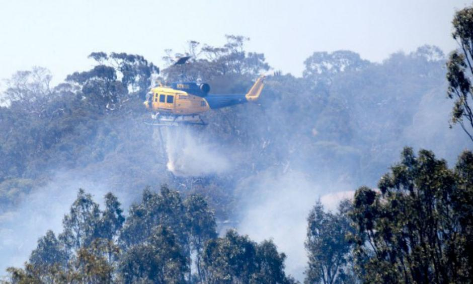 A helicopter helps the effort to control a fire in Sunbury on Christmas Day. Photo: Simon O'Dwyer