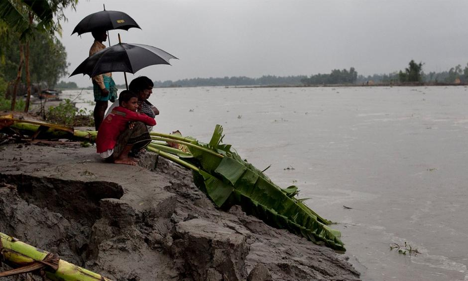 Men look out onto a river that was a farmer's field in the Kalashuna village in Gaibandha district of Bangladesh. Photo: Allison Joyce/Getty Images