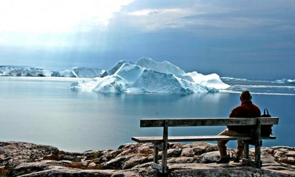 An old man looks out on a Greenland glacier. (Flickr/Goran Ingman)