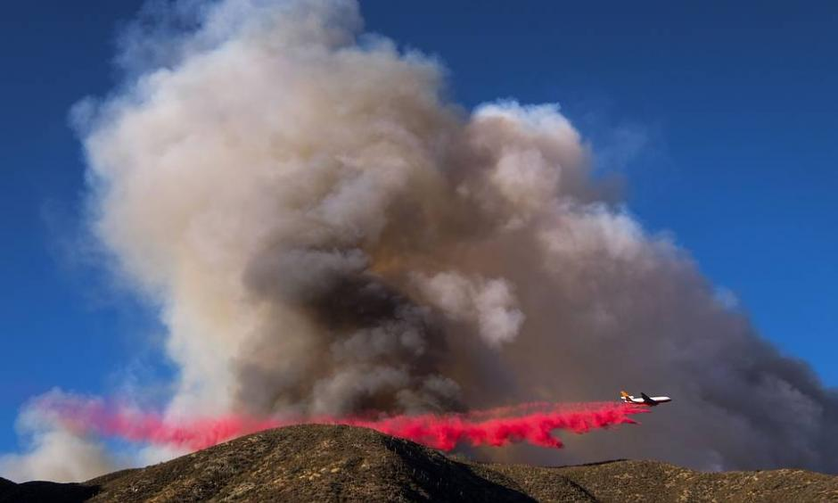An air tanker dropped fire retardant on what has been named the Blue Cut wildfire in Lytle Creek, Calif., on Tuesday. About 700 personnel are involved in containment and evacuation efforts, officials say. Photo: Ringo Chiu, Agence France-Presse, Getty Images
