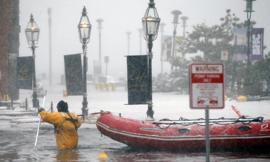 A Boston firefighter wades through flood waters from Boston Harbor on Long Wharf on Thursday, Jan. 4, 2018, after Winter Storm Grayson's storm surge brought the highest coastal water levels ever recorded in Boston. Photo: Michael Dwyer, AP