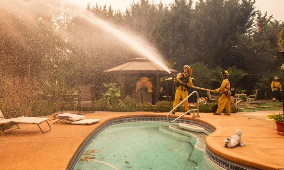 Firefighters spray water on a spot fire at a home during the Kincade Fire on Vinecrest Road in Windsor, Calif., on Sunday, Oct. 27, 2019. Credit: The Weather Channel