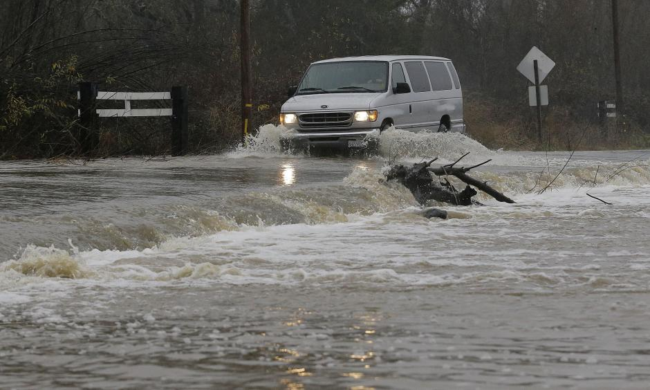 A van drives through flooded water on Green Valley Road in Graton, Calif., Saturday, Jan. 7, 2017. On the California coast, weather forecasters anticipate a storm surge from the Pacific called an atmospheric river to dump several inches of rain from Sonoma to Monterey counties, and up to a foot in isolated places in the Santa Cruz mountains. Photo: Jeff Chiu, AP