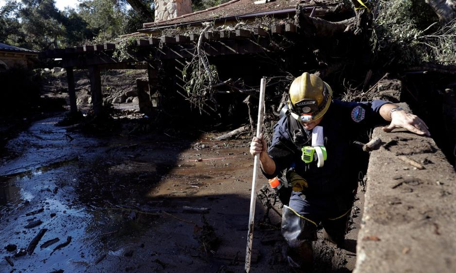 Alex Broumand of the Montecito Fire Department walks in mud in front of homes damaged from storms in Montecito, Calif. on Thursday. Rescue workers used long poles to probe knee-deep ooze for bodies Thursday. Photo: Marcio Jose Sanchez, AP