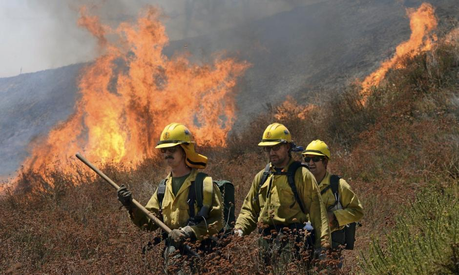 Firefighters battle the Bluecut Fire along Swarthout Canyon Road in the Cajon Pass, north of San Bernardino, Calif., Tuesday August 16, 2016. The blaze 60 miles east of Los Angeles has burned what appear to be several ranch outbuildings and forced evacuations in and around Lytle Creek. Photo: Will Lester / The Sun via Associated Press