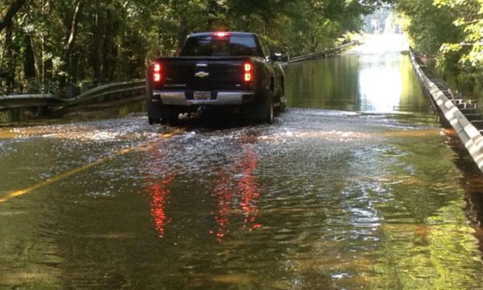 A truck goes through a flooded road. Photo: Venton Blantin