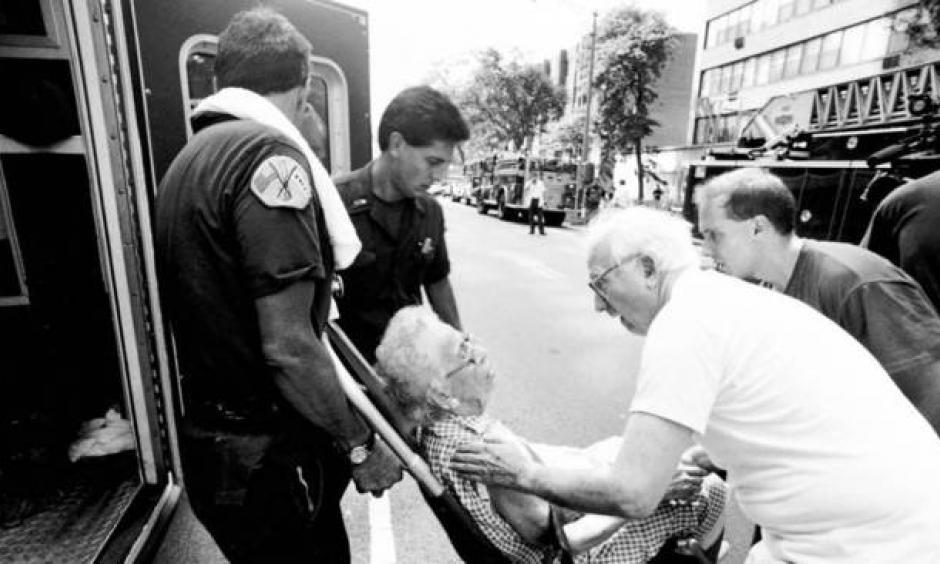 A 101-year-old woman is assisted after being overcome by heat later in the summer when an electrical fire knocked out the power in her apartment building. Photo: Chicago Tribune