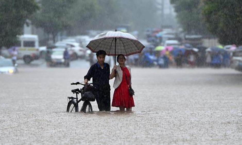 In this Wednesday, July 6, 2016 photo, a couple holding an umbrella in a rain wade through a flooded road in Wuhan in central China's Hubei province. Photo: Chinatopix via AP