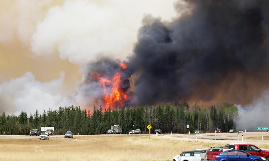 A convoy of evacuees drives south as flames and smoke rise along the highway near Fort McMurray, Alberta, on May 6. Photo: Getty Images