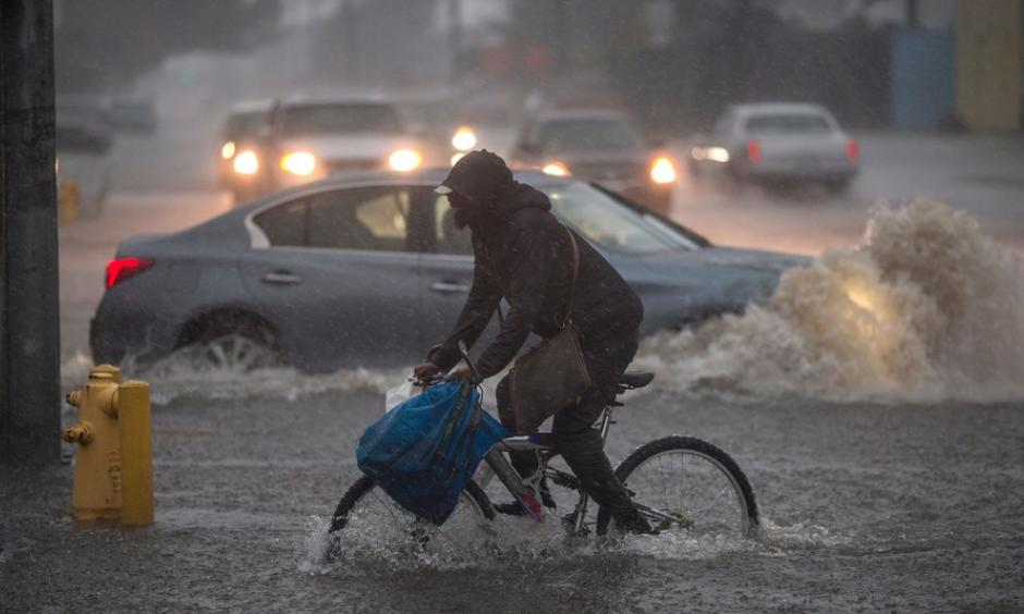 A bicyclist in Sun Valley rides along a flooded street as powerful atmospheric river storms move across California. Photo: David McNew, Getty Images