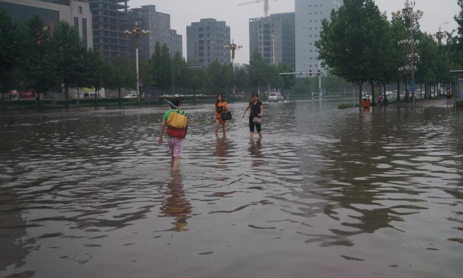Chinese residents wading through floodwaters. Currently, global average annual flood losses are estimated at $104 billion. Photo: Language Teaching Flickr, CC BY 2.0