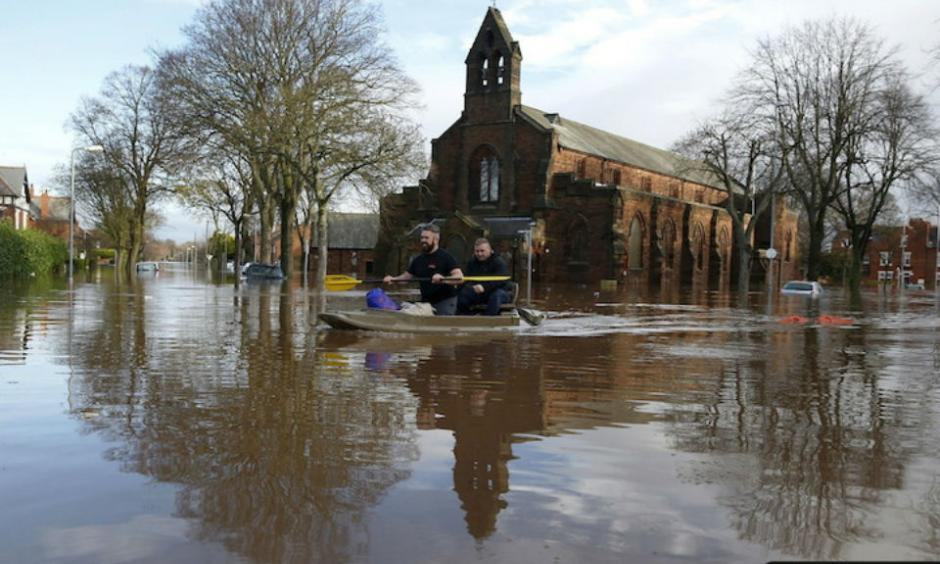 Local residents canoe through flood water as they help to rescue people on a residential street in Carlisle, Britain on Dec. 6, 2015. Photo: REUTERS/Phil Noble