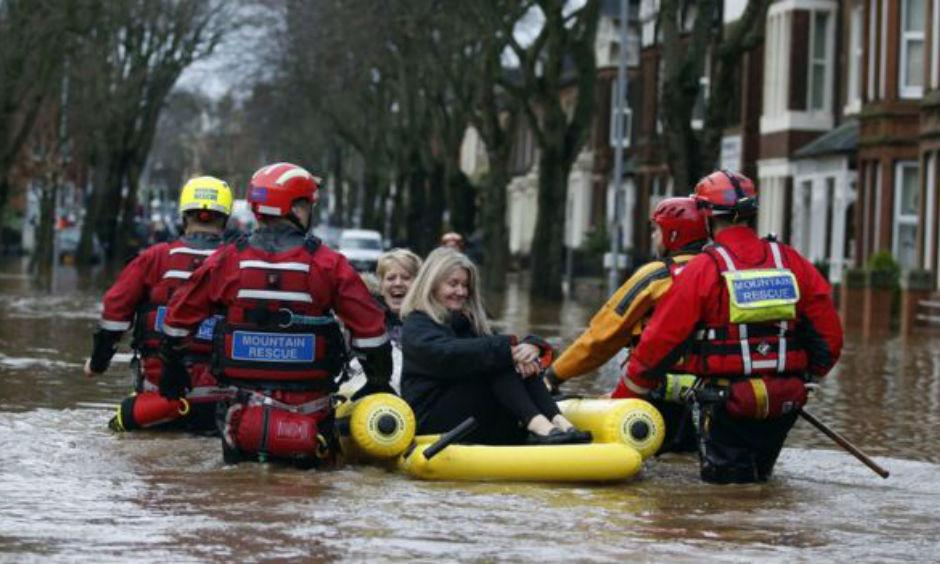 Emergency workers use an inflatable raft to rescue two women from flooding. Photo: BBC