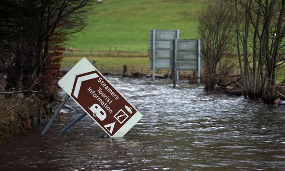 Flood water surrounds a damaged road sign as it covers a road at the northern end of Ullswater, near Pooley Bridge. Photo: Paul Ellis/AFP/Getty Images
