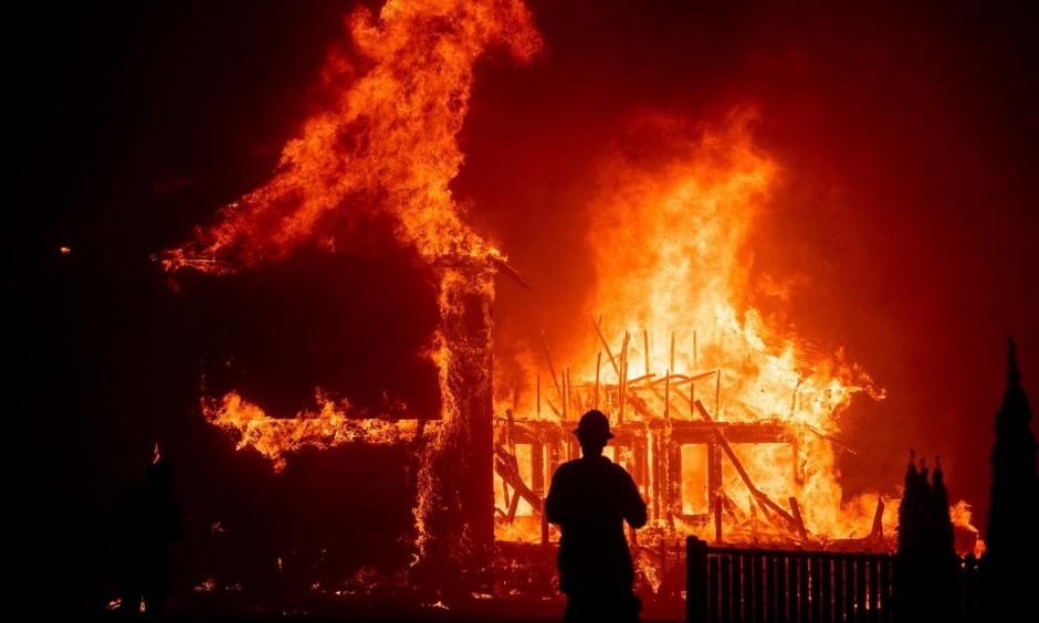A home burns as the Camp Fire rages through Paradise, Calif., in November 2018. Credit: Noah Berger, Associated Press