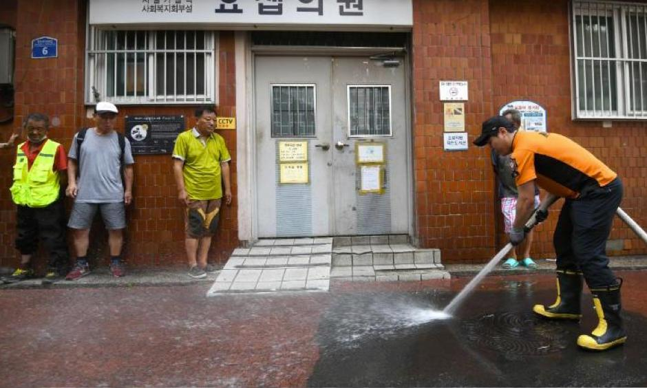 A firefighter sprays water in an alley of a residential district in Seoul to help ease the summer heat. Photo: Jung Yeon-Je, AFP/Getty Images