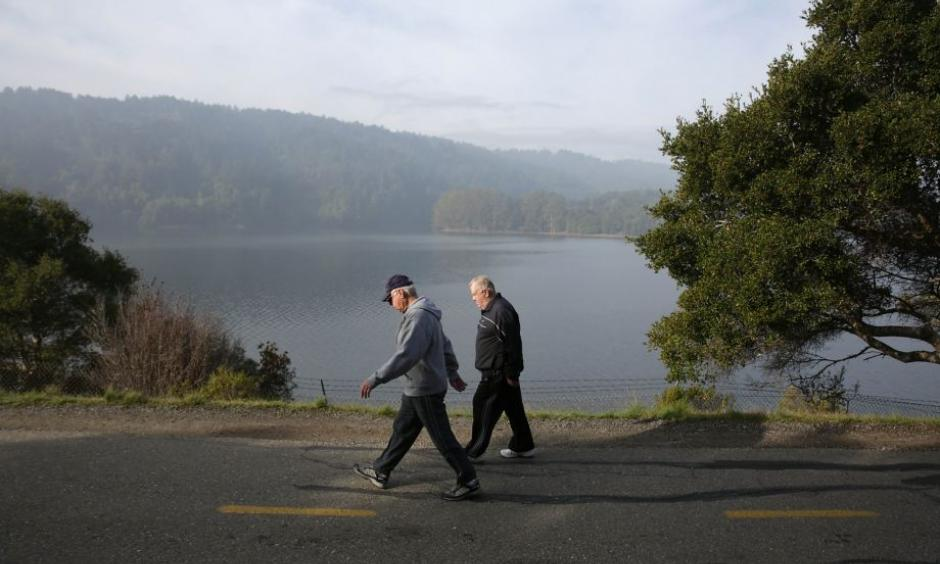 People walk along a path next to Crystal Springs Reservoir, which is starting to show a slow return to normal. Photo: Photo: Lea Suzuki, The Chronicle