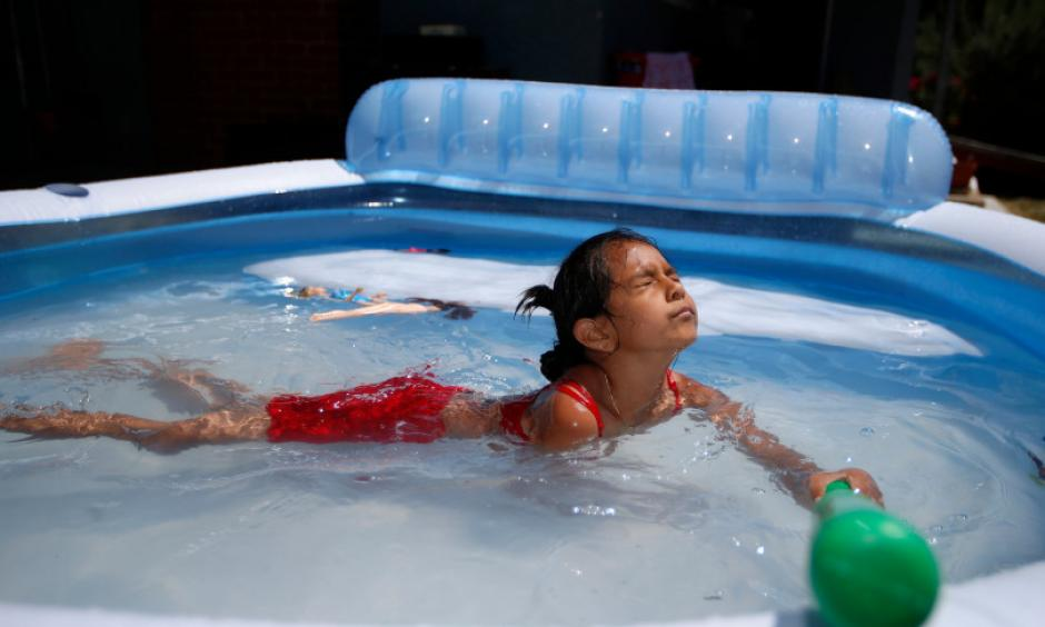 Windy Tinoco, 7, enjoys her family's outdoor inflatable pool in the front yard of their home in the Burbank neighborhood in San Jose, Calif., on Sunday, June 18, 2017. Photo: Nhat V. Meyer, Bay Area News Group