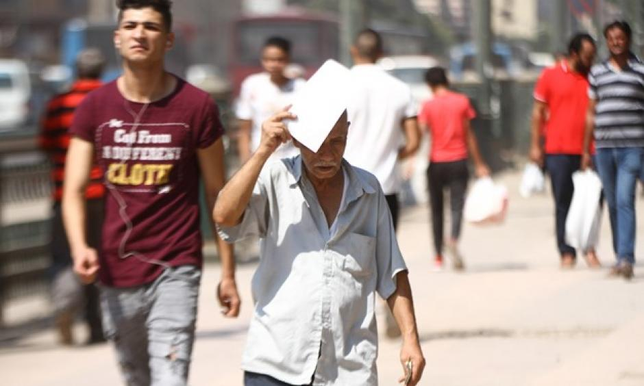 FILE - An Egyptian man covers his head with a paper to avoid the sun rays amid high temperature in Cairo- the photo was taken on August 3, 2018. Photo: Mohamed Fawzy, Egypt Today