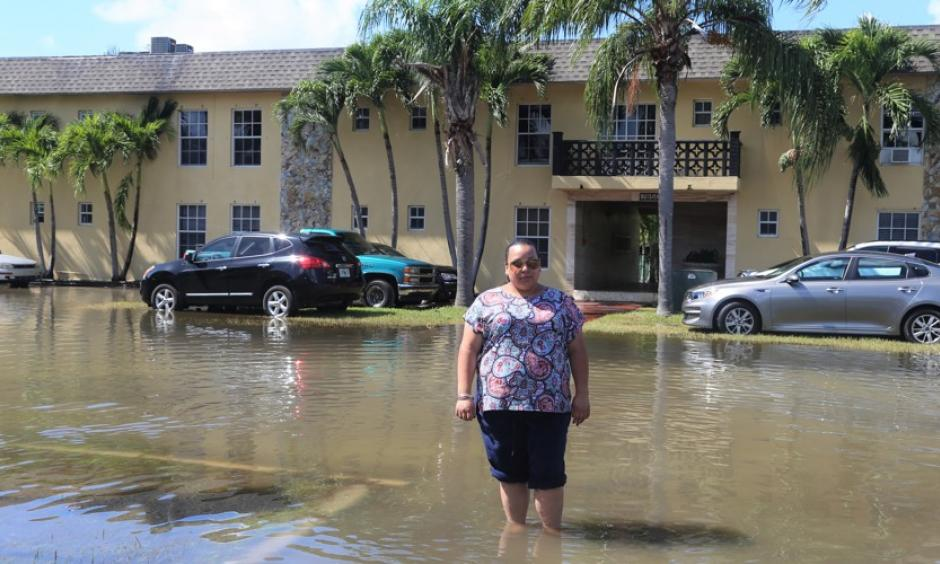 Karina Castillo, an activist for the group Mom's Clean Air Force, standing in tidal flooding in Shorecrest, Miami. Photo: Dayna Reggero for Clean Air Moms Action