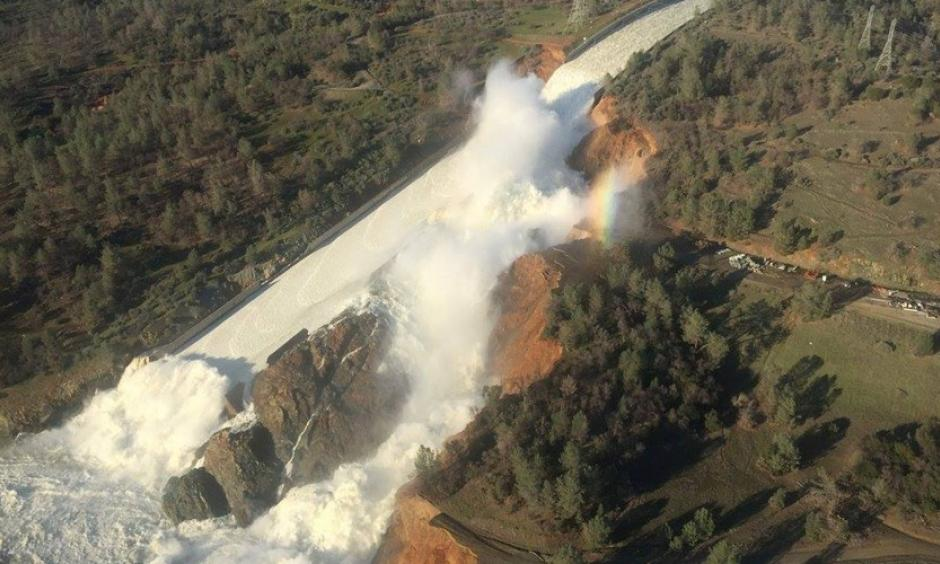 Water pours over the damaged main spillway at the Oroville Dam and over a hillside. Photo: California Department of Water Resources